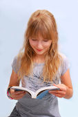 Young girl reading a book — Stockfoto
