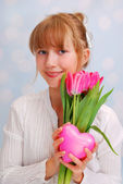 Beautiful young girl with pink tulips and heart — Stock Photo