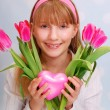 Beautiful young girl with pink tulips and heart - Stock fotografie