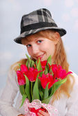 Beautiful girl in hat with tulips — Stock Photo