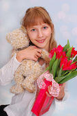 Beautiful girl with teddy bear and tulips — Stock Photo