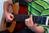 Young boy playing guitar — Stock Photo