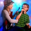 Young girl playing guitar and boy singing — Foto Stock #25014385