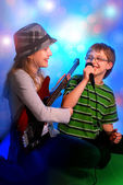 Young girl playing guitar and boy singing — Stock Photo