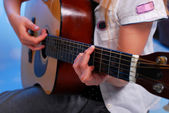 Young girl playing acoustic guitar on the stage — Stock Photo