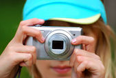 Girl taking photos by digital camera — Stock Photo