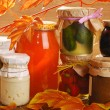 Jars of homemade preserves in autumn scenery — Stock Photo