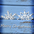 Christmas card with snowflakes on blue wooden background — Stock Photo