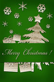 Card with christmas symbol shapes cut from vintage music sheets — Stock Photo