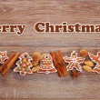 Christmas border with gingerbread cookies and spices on wooden b — Stock Photo