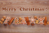 Christmas border with gingerbread cookies and spices on wooden b — Stockfoto
