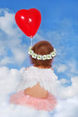 Baby girl with wings sitting on cloud with balloon — Zdjęcie stockowe