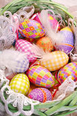 Easter basket with colorful eggs and feathers — Stock Photo