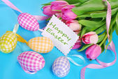 Easter eggs with greeting card and tulips — Stock Photo