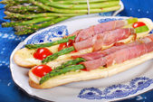 Baguette with green asparagus wrapped in ham — Stock Photo