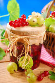 Fresh berries and jar of preserve — Stock Photo
