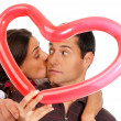 Young couple kissing through balloon heart surprise isolated — 图库照片 #8767882