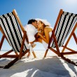 Summer beach kissing couple sitting on deck chairs enjoying an intimate moment — Stock Photo #28392657