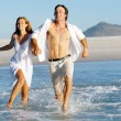 Beach run splash couple — Stock Photo #28392743