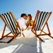 Summer beach kissing couple sitting on deck chairs enjoying an intimate moment — Stock Photo