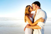 Newlywed couple kissing on honeymoon, beach vacation in summer and an intimate moment. — Stock Photo