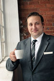 Suit man drinks coffee and thinks — Stock Photo