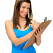 Young woman writing on clipboard — Stock Photo #28402975