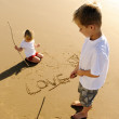 Kids writing in sand — Stock Photo