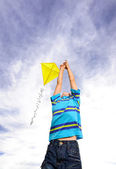 Child reaches high for his kite — Stock Photo