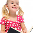 Little girl reads book and smiles — Stockfoto