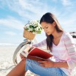 Beach bicycle woman reading book — Stock Photo #28418347