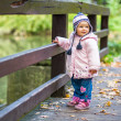 Infant baby girl in golden autumn park — Stock Photo