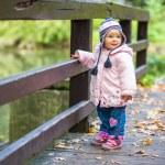 Infant baby girl in golden autumn park — Stock Photo