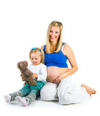 Pregnant woman with 2 yo daughter on white — Stock Photo