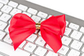 Keyboard with red bright bow. — Stock Photo