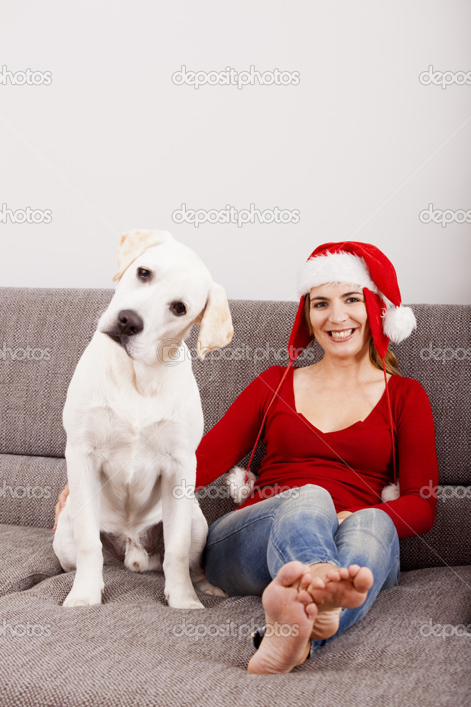 Woman sitting on the sofa with her dog and wearing a santa hat   — Stock Photo #12865785