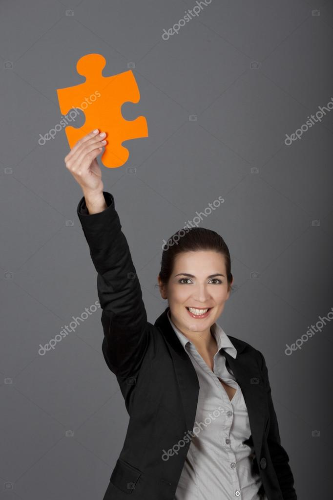 Business woman holding a big puzzle piece, over a gray background — Stock Photo #12872269