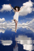 Girl jumping over the water — Stock Photo