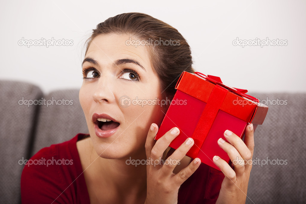 Beautiful and happy woman trying to guess what is inside the christmas present — Stock Photo #14933755