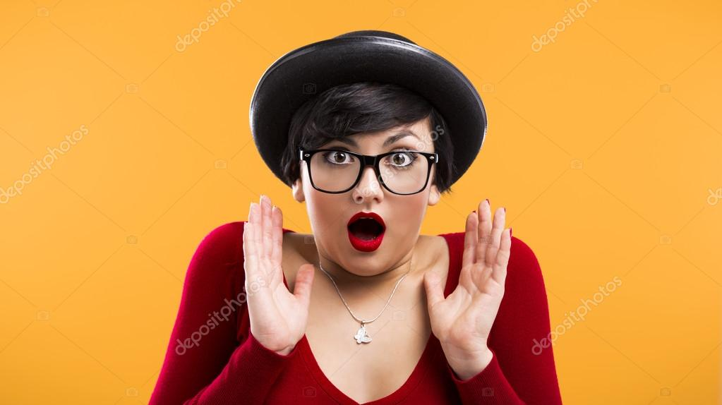 Beautiful girl with a astonished expression, wearing a hat and nerd glasses over a yellow background — Stock Photo #19121867