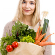 Beautiful woman carrying vegetables — Stock Photo