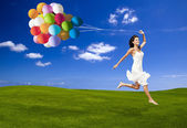 Jumping with a colored ballons — Photo
