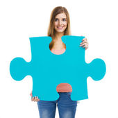 Woman holding a puzzle piece — Stock Photo