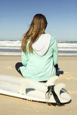 Girl sitting in the beach and checking the waves — Stock fotografie