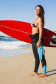 Surfer girl with her surfboard — Stock Photo