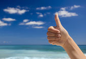 Thumbs up against a blue sky — Stock Photo
