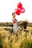 Woman with  bike and balloons — Stock Photo