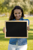 Beautiful woman holding a shalkboard — Stock fotografie