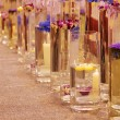 Foto Stock: Row of different vases with flowers and candles