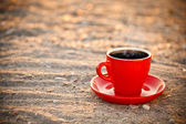 Coffee cup on sand — Stock Photo
